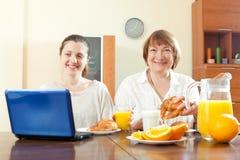 Женщины используя компьтер-книжку во время завтрака Стоковая Фотография