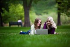 Женщины используя компьтер-книжку в парке Стоковые Изображения
