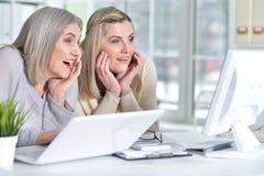 Женщины используя компьтер-книжку и компьютер Стоковое Фото