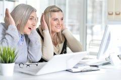 Женщины используя компьтер-книжку и компьютер Стоковое Изображение RF