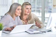 Женщины используя компьтер-книжку и компьютер Стоковые Фотографии RF