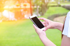 Женщины используя мобильный телефон в тоне года сбора винограда парка Стоковое Изображение RF