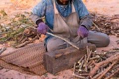Женщины используя нож к прерванному дереву кассавы Стоковые Изображения