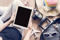 Женщины используя таблетку и подготавливают путешествовать Стоковые Изображения