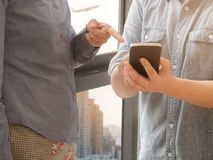 2 женщины используя умный телефон в офисе с backgro нерезкости здания Стоковое фото RF