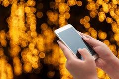 Женщины используя умный телефон на запачканном свете Стоковое Изображение RF