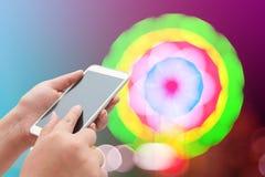 Женщины используя умный телефон на запачканном свете Стоковое Фото