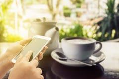 Женщины используя умный телефон на кофейне Стоковое Фото