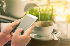 Женщины используя умный телефон на кофейне Стоковые Изображения RF