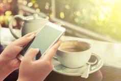 Женщины используя умный телефон на кофейне Стоковое Изображение