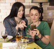 2 женщины используя умный телефон Стоковое Изображение