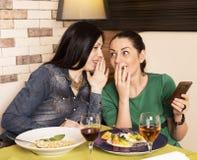 2 женщины используя умный телефон Стоковые Фотографии RF