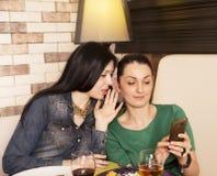 2 женщины используя умный телефон Стоковая Фотография RF