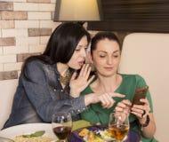 2 женщины используя умный телефон Стоковая Фотография