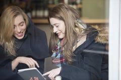 Женщины используя цифровую таблетку в кафе Стоковое Изображение