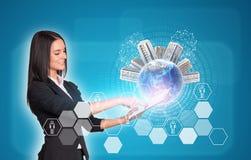 Женщины используя цифровую таблетку Земля с зданиями Стоковые Изображения RF