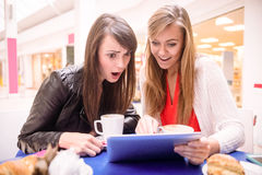 Женщины используя цифровую таблетку пока имеющ кофе и закуски Стоковое Изображение