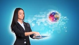 Женщины используя цифровые таблетку и землю с миром Стоковая Фотография