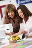 2 женщины используя электрическую швейную машину Стоковые Изображения
