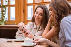 Женщины используя smartphone в кафе Стоковые Фотографии RF
