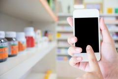 Женщины используя smartphone в фармации Стоковое Изображение