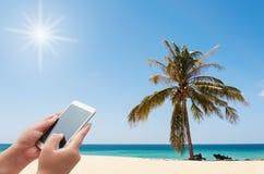 Женщины используя smartphone на пляже Стоковая Фотография RF