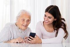 2 женщины используя Smartphone дома Стоковая Фотография RF
