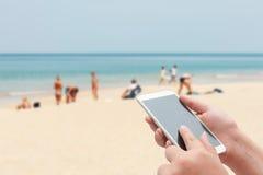 Женщины используя smartphone покрывают на запачканном голубом море и белый песок Стоковые Изображения