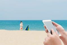 Женщины используя smartphone покрывают на запачканном голубом море Стоковая Фотография