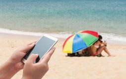 Женщины используя smartphone покрывают на запачканном голубом море Стоковое Изображение RF