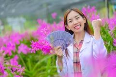 Женщины исследователей, радостны преуспеть в розовых садах орхидеи в саде для экспорта стоковое изображение