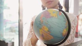 Женщины исследуют глобус для того чтобы запланировать их отключение Стоковые Изображения