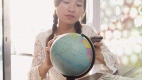 Женщины исследуют глобус для того чтобы запланировать их отключение Стоковое Фото