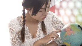 Женщины исследуют глобус для того чтобы запланировать их отключение Стоковое Изображение RF