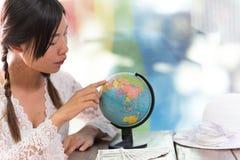 Женщины исследуют глобус для того чтобы запланировать их отключение Стоковые Фотографии RF
