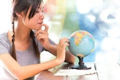 Женщины исследуют глобус для того чтобы запланировать их отключение Стоковое Изображение