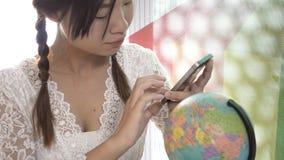 Женщины исследуют глобус для того чтобы запланировать их отключение Стоковая Фотография