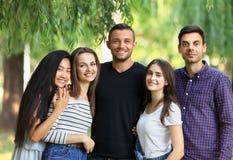 5 женщины и друзей людей на зеленой предпосылке леса Стоковое фото RF