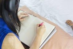 Женщины или девушка сидят на кровати, слушают к музыке и писать вниз на bl Стоковые Фото