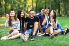 5 женщины и людей друзей надувают пузырь мыла outdoors Стоковое Изображение