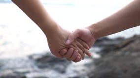 Женщины и люди пар замедленного движения соединяют руки на пляже для того чтобы чувствовать теплыми Романтичный и любящий как кон акции видеоматериалы