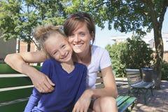 Женщины и маленькая девочка сидят на стенде Стоковая Фотография