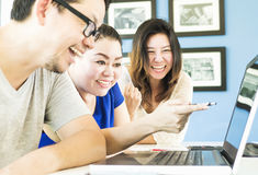 2 женщины и один человек счастливо смотрят компьютер Стоковое Фото