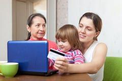 Женщины и ребенок оплачивая кредитной карточкой в интернете Стоковое фото RF