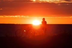 Женщины и силуэты bike на пляже на заходе солнца Стоковые Изображения RF