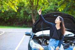 Женщины и сломали вниз с автомобиля на дороге и он находит мобильный телефон сигнала стоковое изображение rf