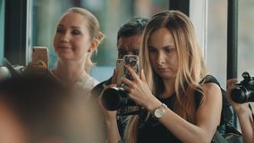 Женщины и человек собирают киносъемку с камерами и умными телефонами на толпить событие сток-видео