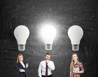2 женщины и человек и большие электрические лампочки Стоковое Изображение