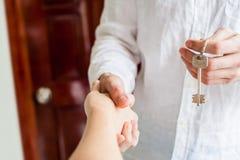 Женщины и человек тряся руки рук только, который нужно увидеть и ключ давались на предпосылке деревянной двери Иметь жулика недви Стоковое Фото