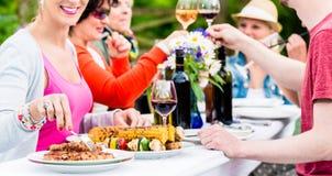 Женщины и люди празднуя приём гостей в саду Стоковое фото RF